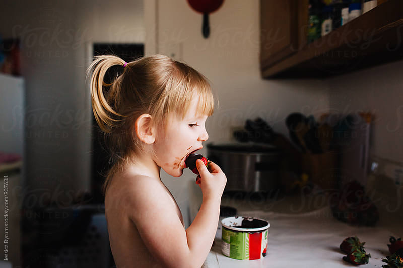 Toddler girl taking a bite of a chocolate covered strawberry by Jessica Byrum for Stocksy United