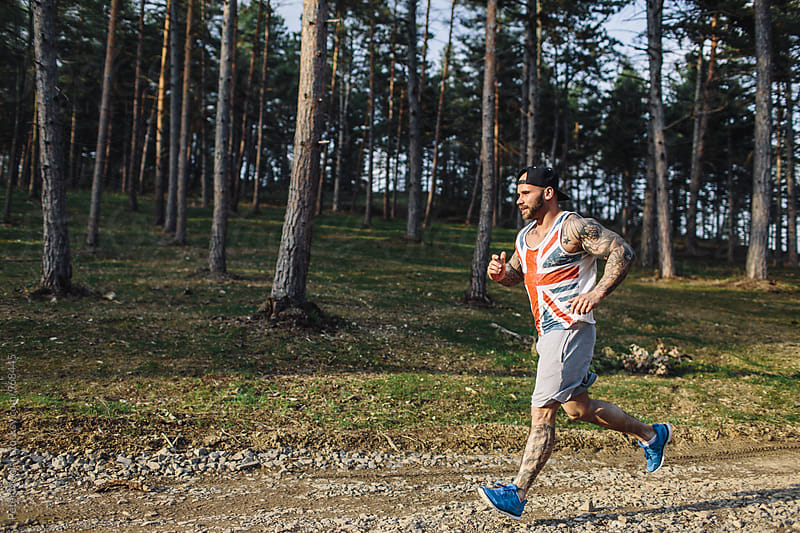 Sporty Tattooed Man Running by Peter Meciar for Stocksy United