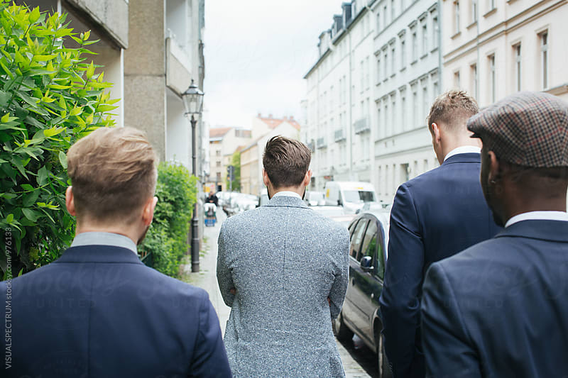 Group of Four Stylish Young Men in Suits Walking Down Street by Julien L. Balmer for Stocksy United