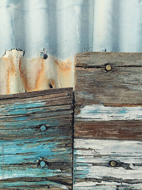 Pieces of old and painted scrap wood against warehouse wall, close up by Paul Edmondson for Stocksy United