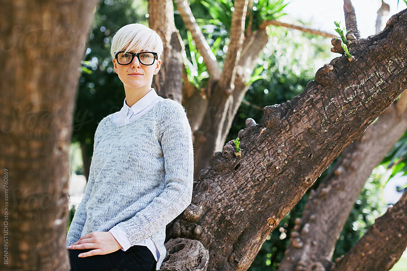 Portrait of a blonde woman sitting on a tree of the park. by BONNINSTUDIO for Stocksy United