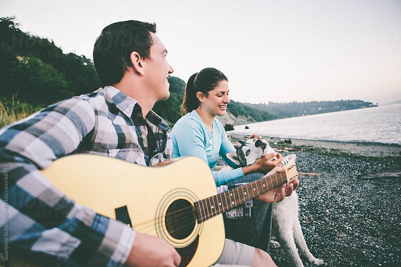 Couple playing guitar while camping on the beach by Suprijono Suharjoto for Stocksy United
