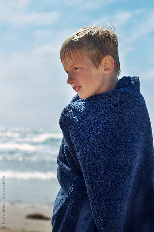 A boy wet from swimming on a beach, wrapped in a towel. by Helen Rushbrook for Stocksy United
