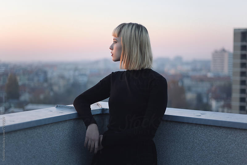 Portrait of a stylish young woman on the roof of the building during sunset by VeaVea for Stocksy United