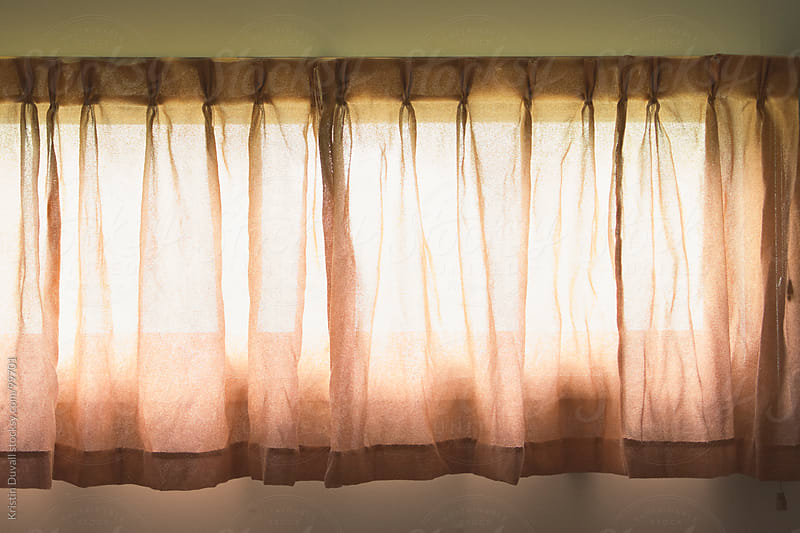 Sunlight through closed curtains by Kristin Duvall for Stocksy United