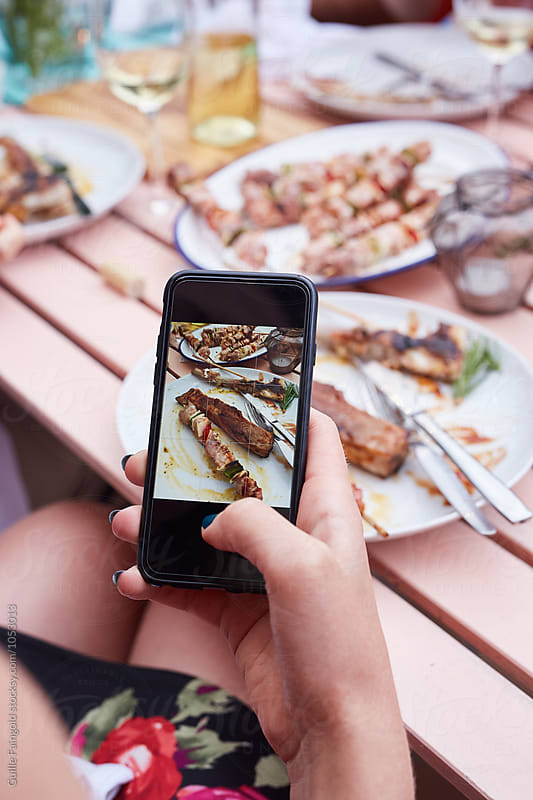 Hand with smartphone taking food photo of grilled meat by Guille Faingold for Stocksy United