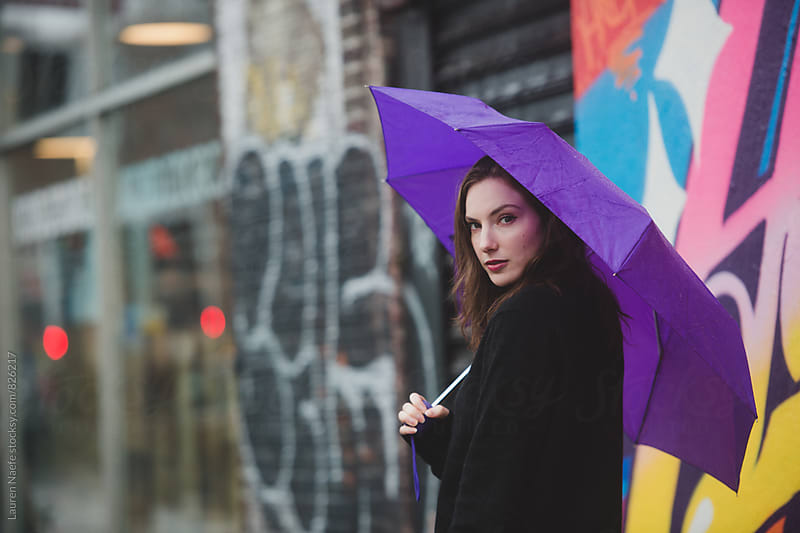 Woman walking in the rain  by Lauren Naefe for Stocksy United