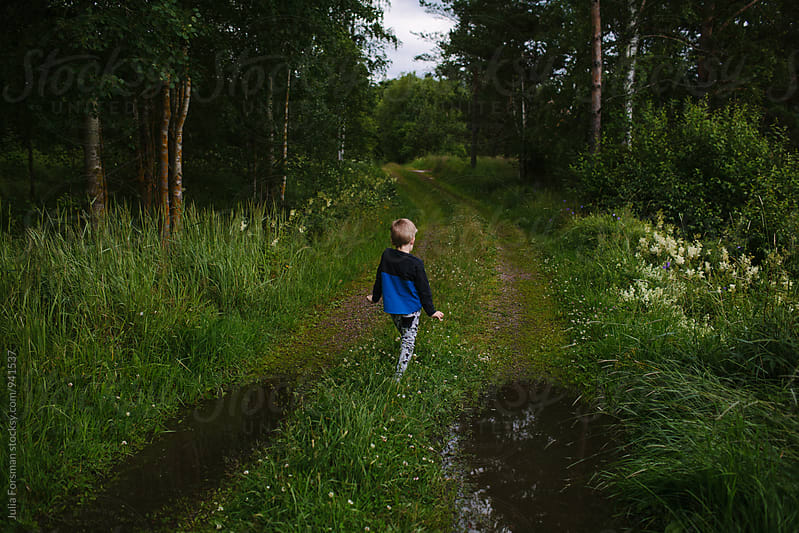 Back of boy dancing as he walks down a beautiful country path. by Julia Forsman for Stocksy United