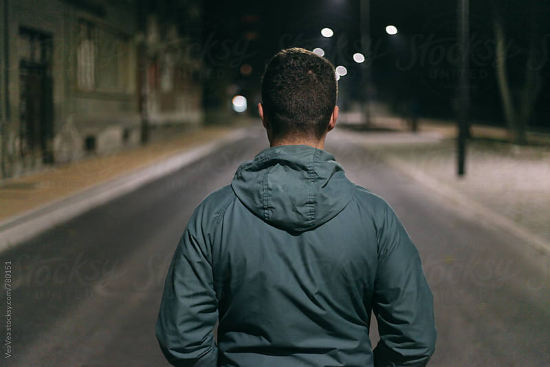 Man in the street during the night from the back  by Marija Mandic for Stocksy United