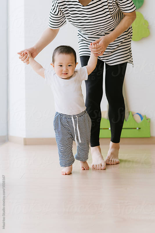 Toddler boy learning to walk with his mother helping him by MaaHoo Studio for Stocksy United