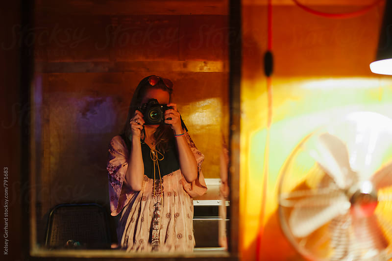 A woman takes a picture of herself in the mirror inside a vintage trailer. by Kelsey Gerhard for Stocksy United