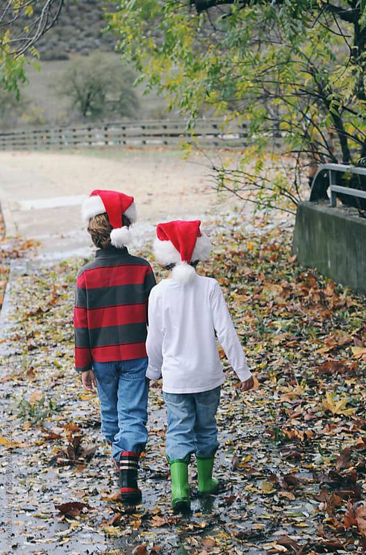 Two boys walking away in leaves wearing Christmas Hats by Monica Murphy for Stocksy United