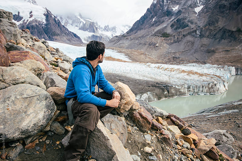 Young hiker man looking to mountains and glacier landscape. Adventure travel by Alejandro Moreno de Carlos for Stocksy United
