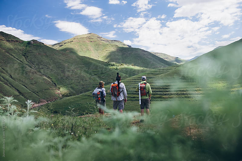 fly fishermen hikers enjoying a mountainous view over a wilderness river by Micky Wiswedel for Stocksy United