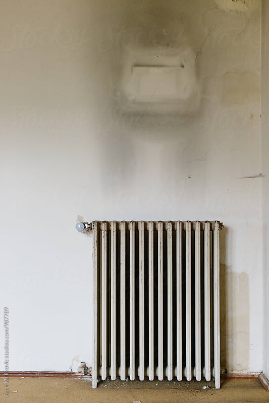 Old cast iron radiator on a grungy wall by Amir Kaljikovic for Stocksy United