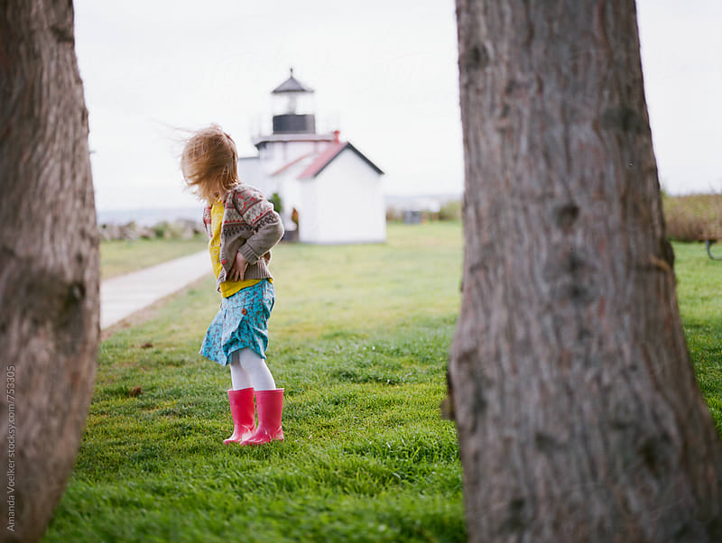 Little Girl Stands Between Trees with a Lighthouse in the Background by Amanda Voelker for Stocksy United