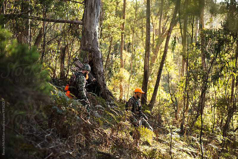 Two Deer Hunters in the Bush by Reece McMillan for Stocksy United