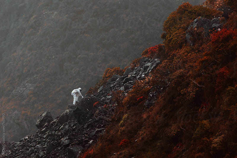 A lone astronaut climbs the side of a rocky mountain  by HOWL for Stocksy United
