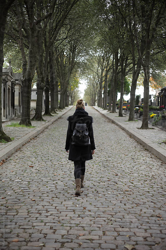 Young woman walking on historic graveyard by Marcel for Stocksy United