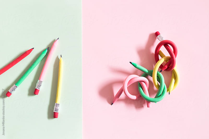 Individual and linked flexible pencils arranged on colorful paper by Jovana Milanko for Stocksy United