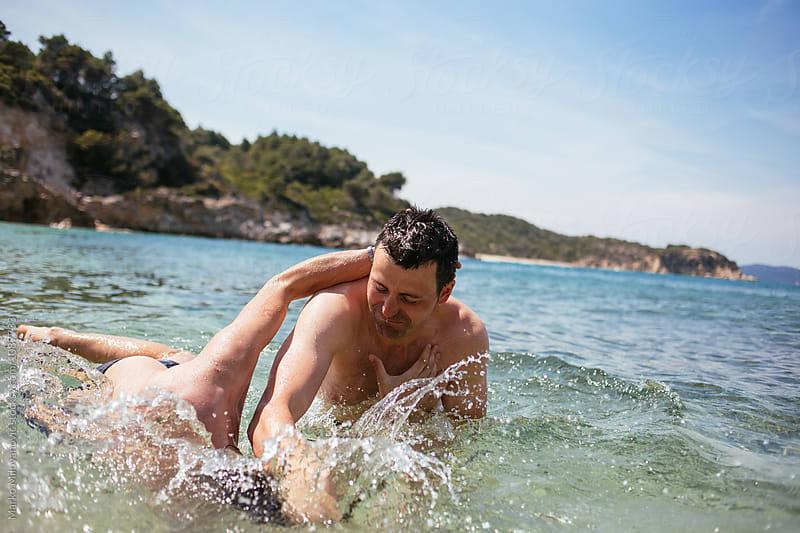 Friends fighting in the sea by Marko Milovanović for Stocksy United