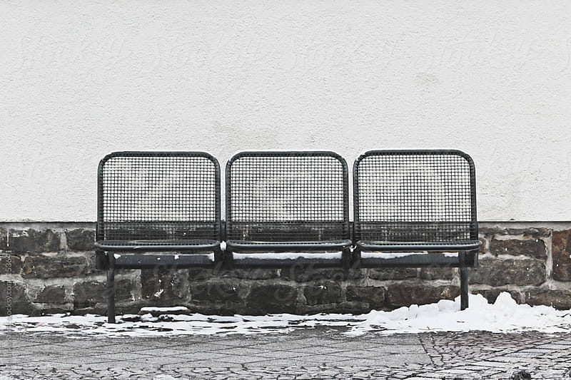 Bench before wall on a snowy day by Melanie Kintz for Stocksy United