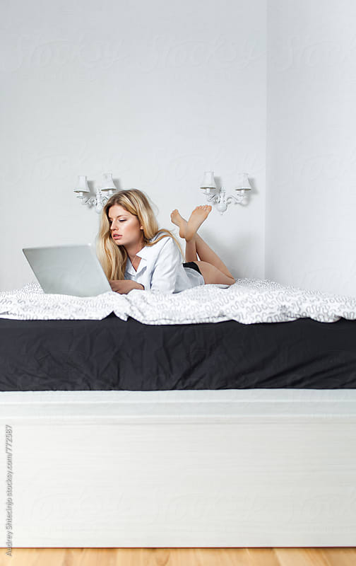 Young sensual blonde female on laptop in her bed  by Audrey Shtecinjo for Stocksy United