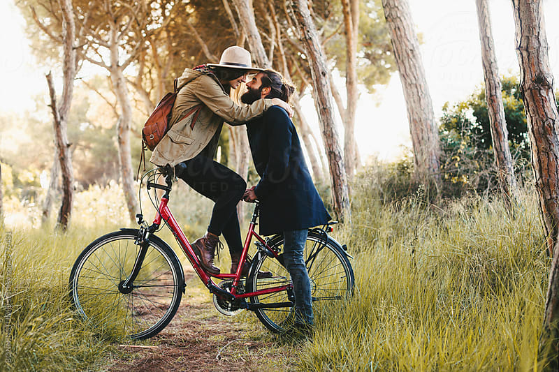 Lovers on a bicycle in the forest.  by BONNINSTUDIO for Stocksy United