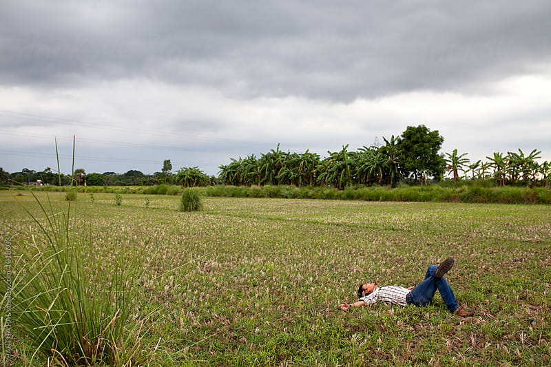 Young man lying on green field by PARTHA PAL for Stocksy United