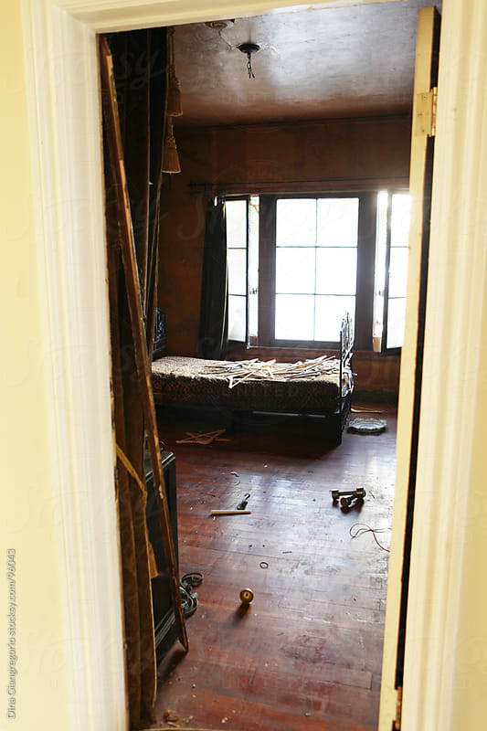 View through doorway of abandoned bedroom  by Dina Giangregorio for Stocksy United