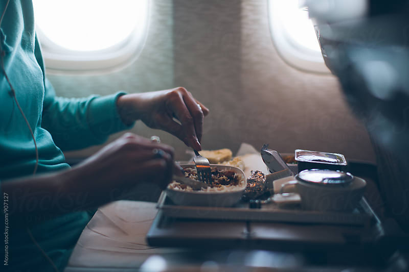 Woman Eating Airplane Food by Mosuno for Stocksy United