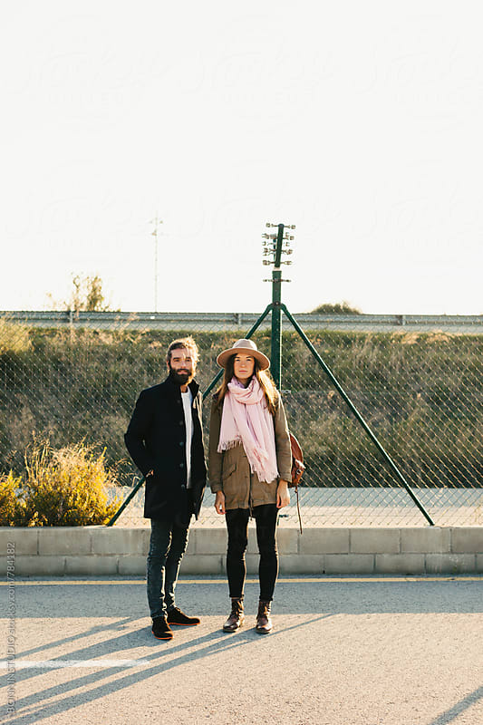 Portrait of a hipster couple standing outside on a sunny day. by BONNINSTUDIO for Stocksy United