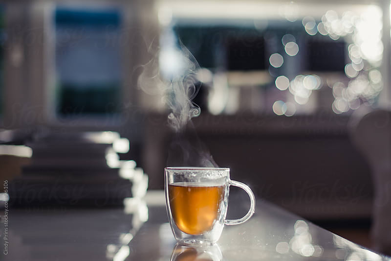 A glass cup of tea with steam standing on a table in the sunlight by Cindy Prins for Stocksy United