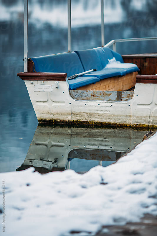 Old vintage wooden boats on a lake at winter by Maja Topcagic for Stocksy United