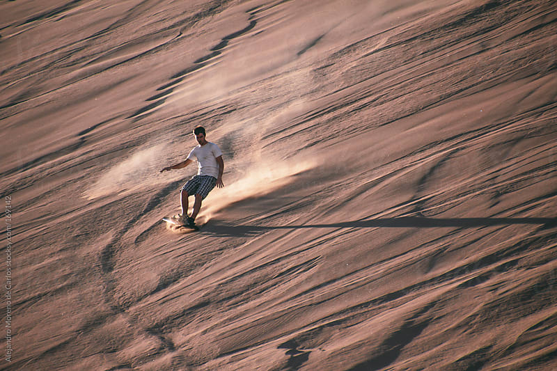 Man doing sandboard on desert dunes by Alejandro Moreno de Carlos for Stocksy United