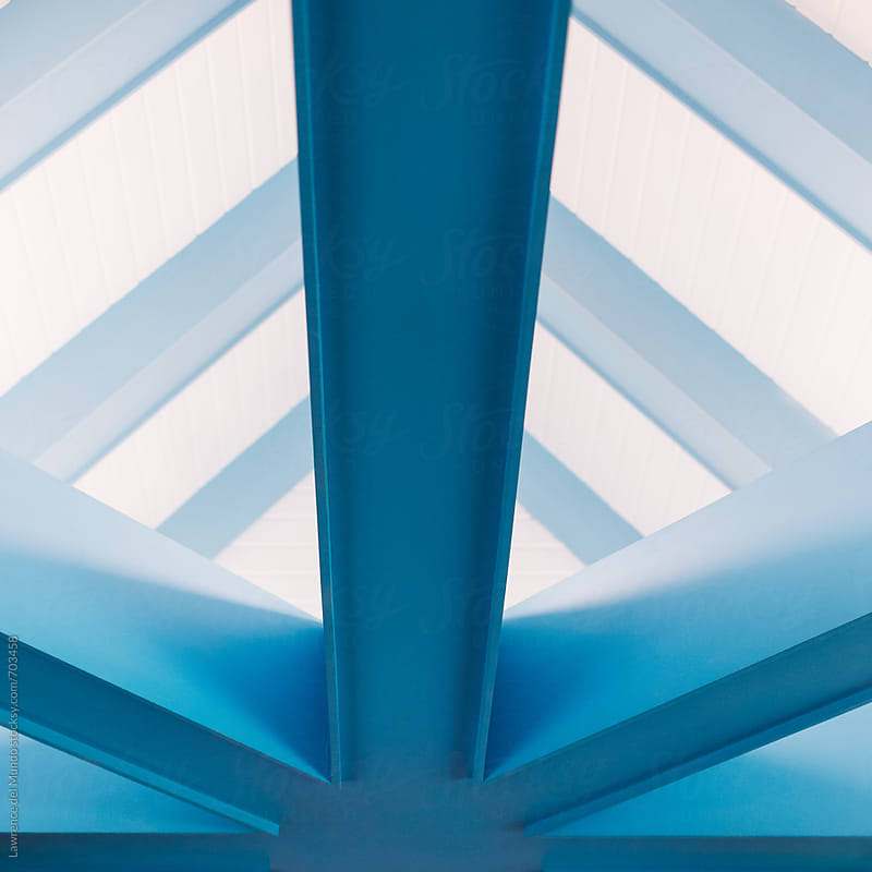 Detail of and closer view of the light on the light blue beams supporting the roof  of a restaurant by Lawrence del Mundo for Stocksy United