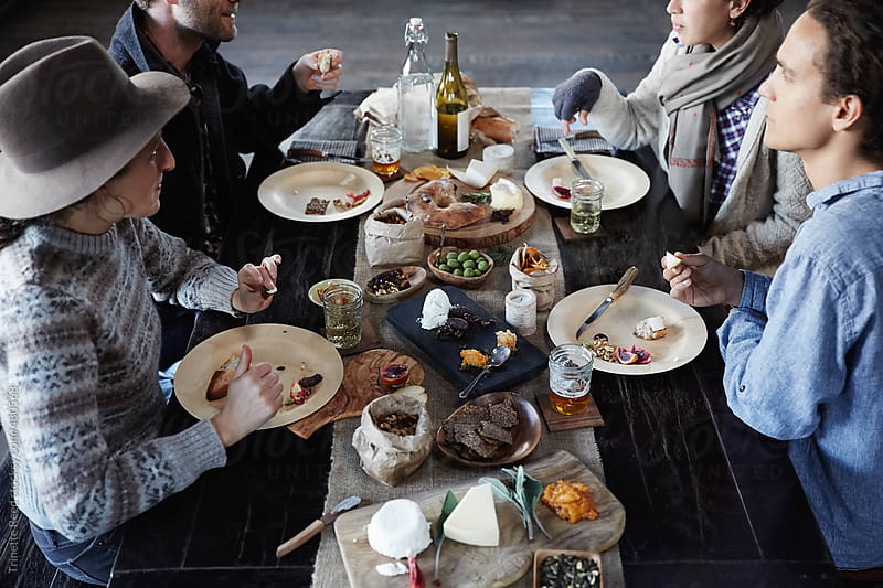 Group of friends having a rustic farm to table picnic in wood barn by Trinette Reed for Stocksy United