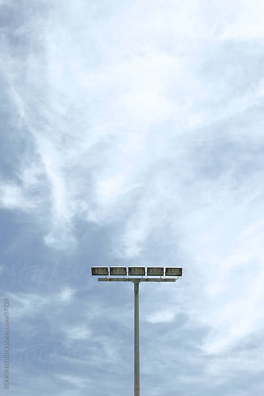 Stadium light over cloudy sky. by BONNINSTUDIO for Stocksy United