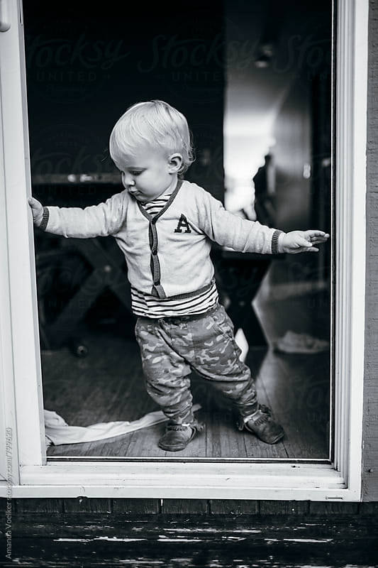 Toddler boy stands in open doorway by Amanda Voelker for Stocksy United