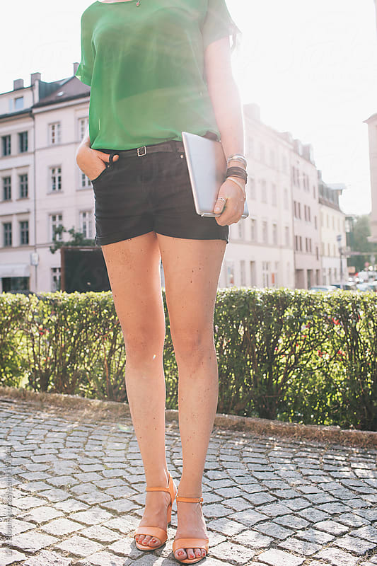 Young, stylish woman, standing in urban environment, carrying a tablet pc. by Lilly Bloom for Stocksy United