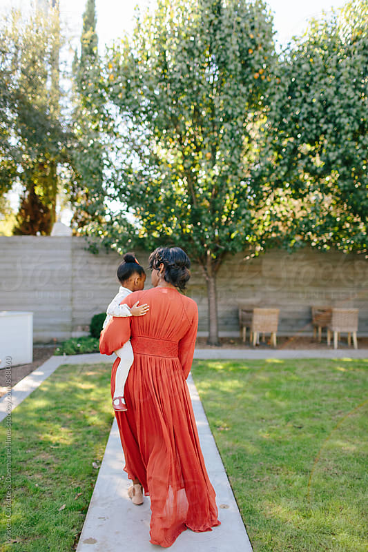 A mother holding her child walking through the park  by Kristen Curette Hines for Stocksy United