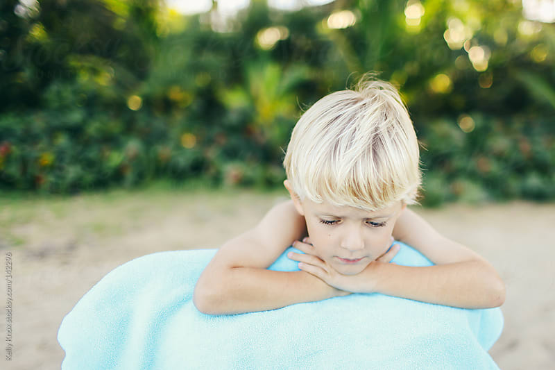 boy resting on the beach by Kelly Knox for Stocksy United