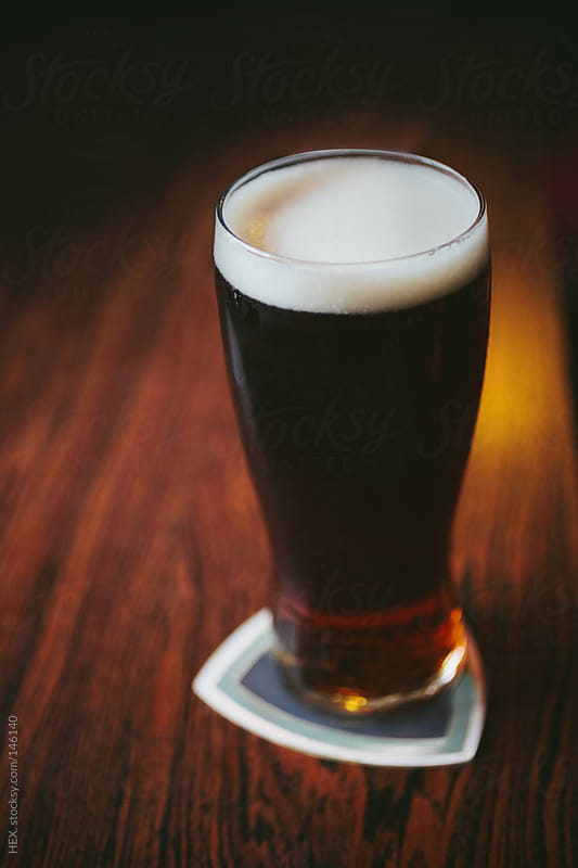 Black Irish Beer On Wooden Table by HEX. for Stocksy United