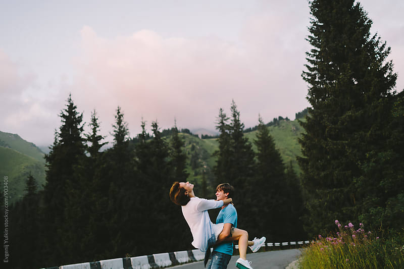 Young couple having fun on the mountain road by Evgenij Yulkin for Stocksy United