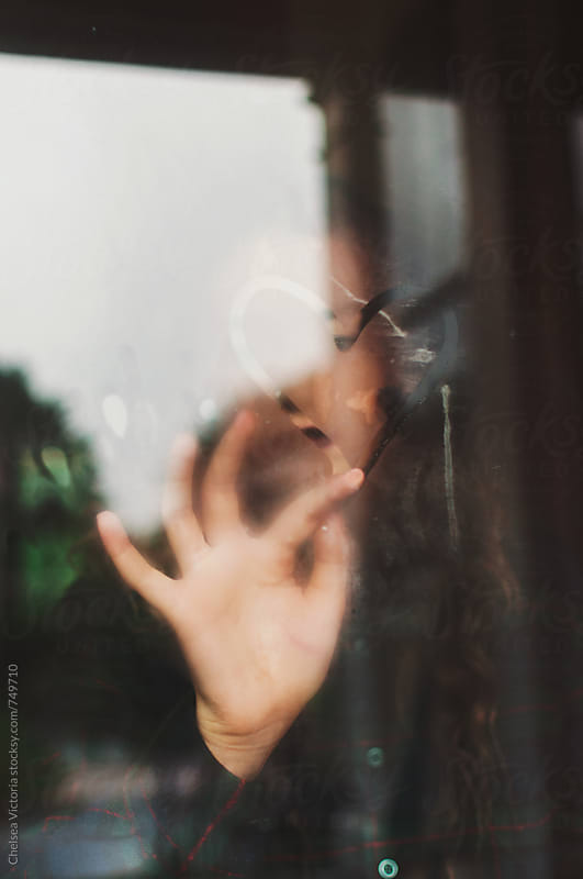 A woman making a heart shape on a window by Chelsea Victoria for Stocksy United