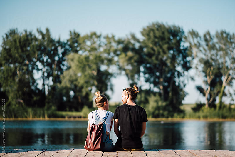 Couple sitting on the wooden dock by the lake  by Boris Jovanovic for Stocksy United