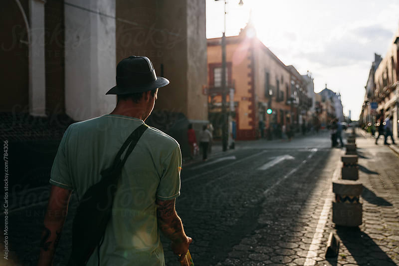 Back view of one young man with a hat walking on a stone street to the village center in Mexico by Alejandro Moreno de Carlos for Stocksy United