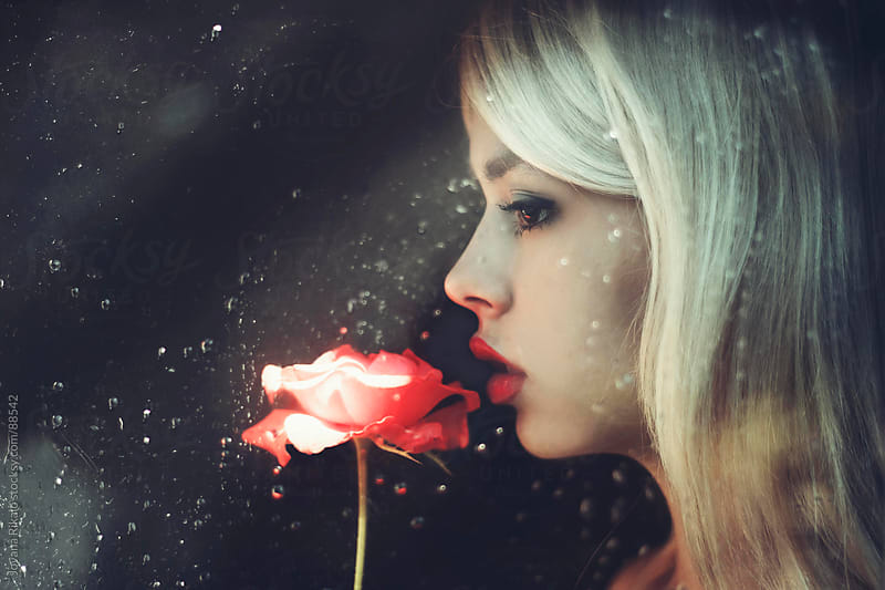 Beautiful girl standing at the window holding the rose by Jovana Rikalo for Stocksy United
