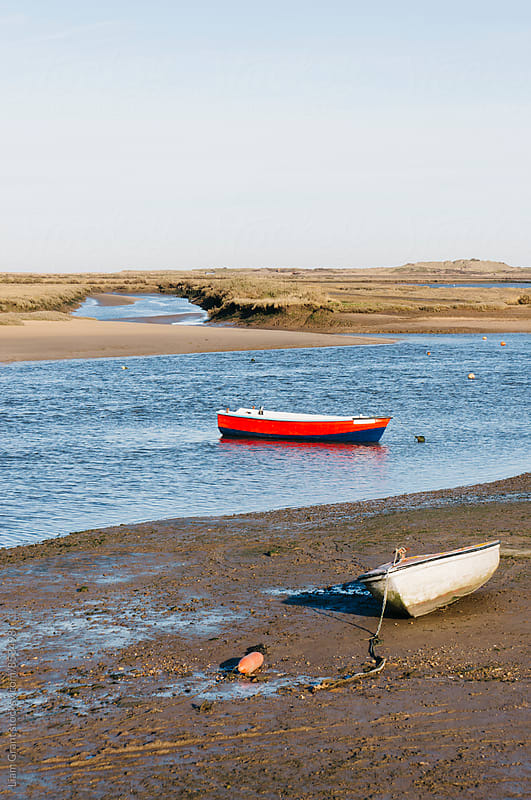 Rowing boats at low tide. Burnham Overy Staithe, Norfolk, UK. by Liam Grant for Stocksy United