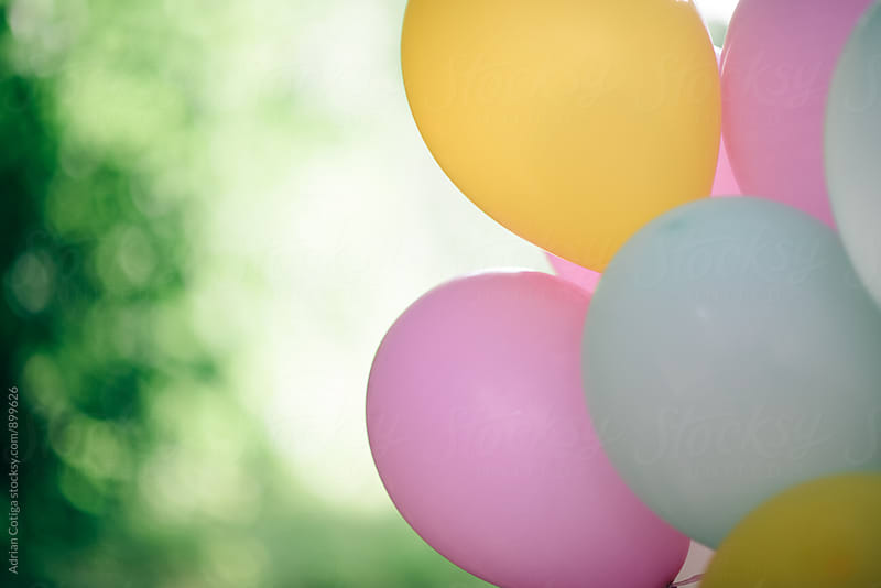 Pastel colored  balloons outdoor with green background by Adrian Cotiga for Stocksy United